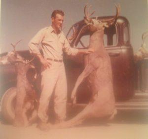 Myron holding up a deer he shot