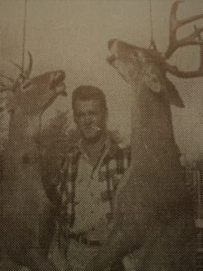 Myron standing by two hanging deer